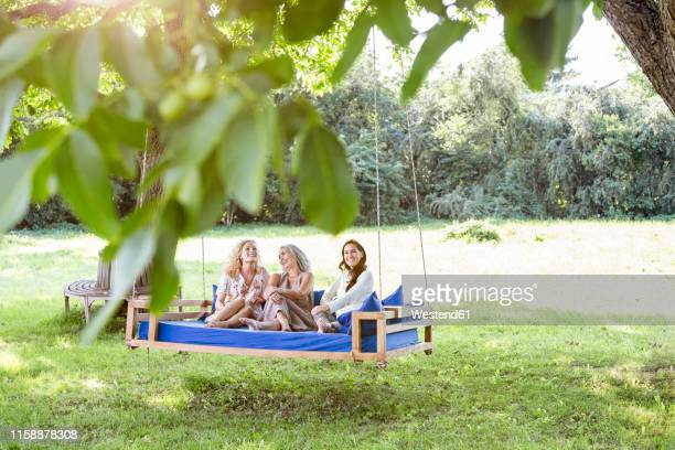 women of a family relaxing in garden, sitting on a swing bed - adults only stock pictures, royalty-free photos & images
