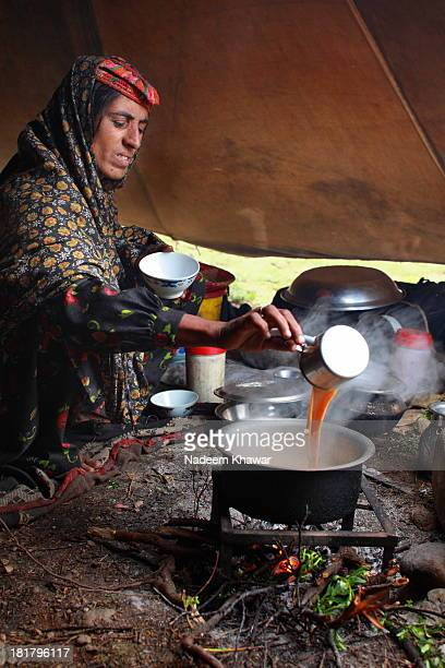 Women of nomad family at Deosai National Park making tea in her tentAs they visit Deosai each year with their herds and stay here until snowfall start