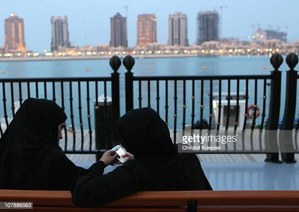 Women of Qatar sit in front of the skyline of the Pearl area on January 5 2011 in Doha Qatar The International Monetary Fund recently reiterated its...