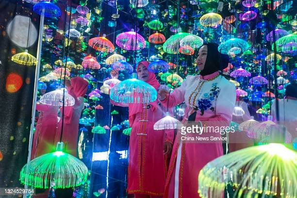 Women of Salar and Dongxiang ethnic minority groups watch light installations on June 19, 2021 in Jishishan County, Gansu Province of China.