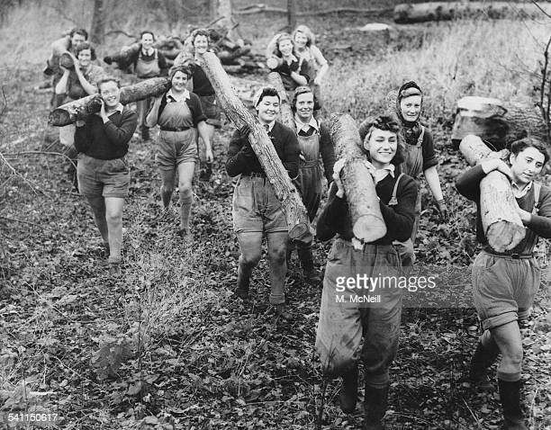 Women of the Forestry Commission section of the Women's Land Army carry logs on their shoulders ready to be stacked at Culford Camp near Bury St...