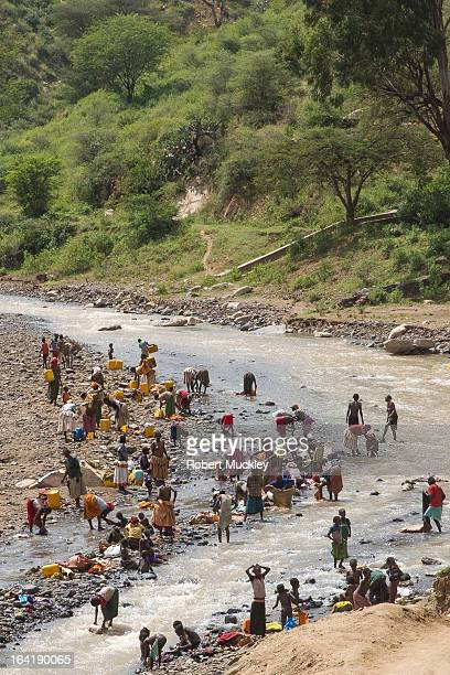 Women of the Konso tribe in traditional yellow and orange dresses collecting drinking water from the riverand washing clothes in the river....
