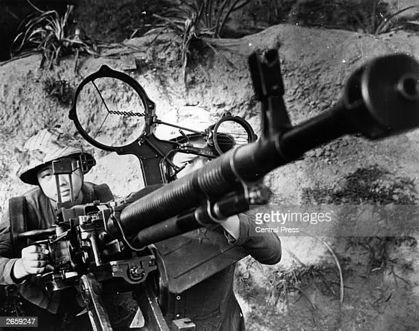 Women of the North Vietnamese Army aiming an antiaircraft gun in a propaganda photograph during the Vietnam War