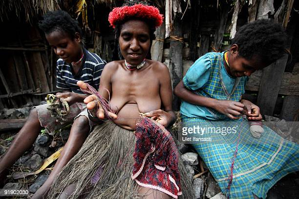 Women of the traditional Dani tribe from Lembah Baliem make a traditional bag called a Noken on October 10 2009 in Wamena West Papua Indonesia The...