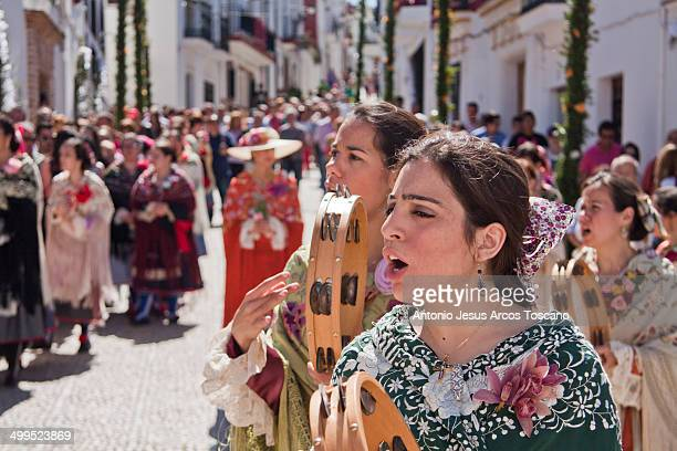 CONTENT] Women of the village of Almonaster la Real Huelva procession through the streets dressed in costumes singing and playing tambourines