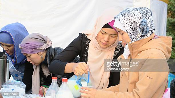 Women offer foods and drinks after people perform the Eid AlAdha prayer at NurAstana Mosque in Astana Kazakhstan on September 12 2016 Muslims...