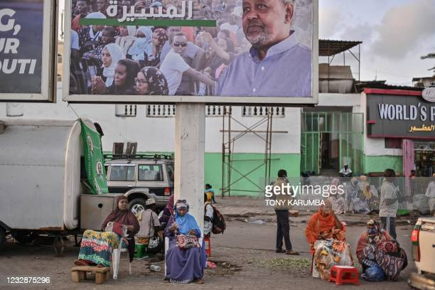 Women offering foreign exchange services sit along an open street with satchels filled with a variety of regional and international currencies,...