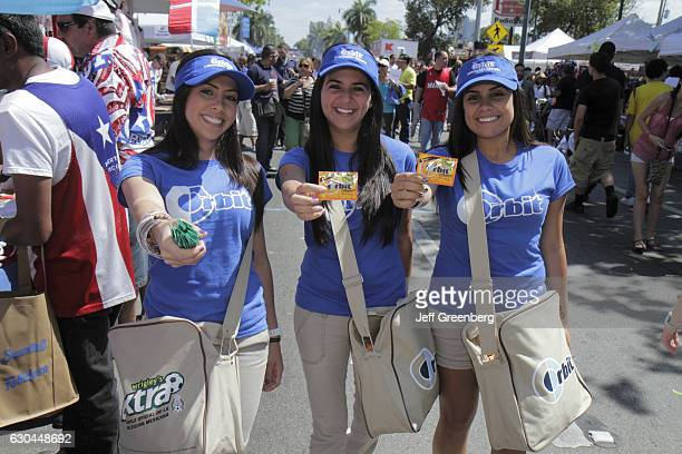 Women offering free samples of Wrigley's gum at the Calle Ocho Street Festival