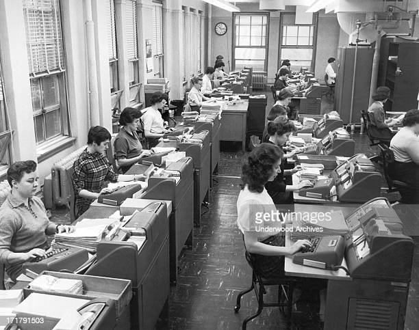 Women office workers entering data using tabulating machines and punch cards at the Erie Railroad Company offices Cleveland Ohio January 22 1958
