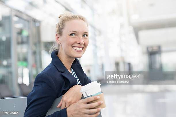 women on airport with coffee