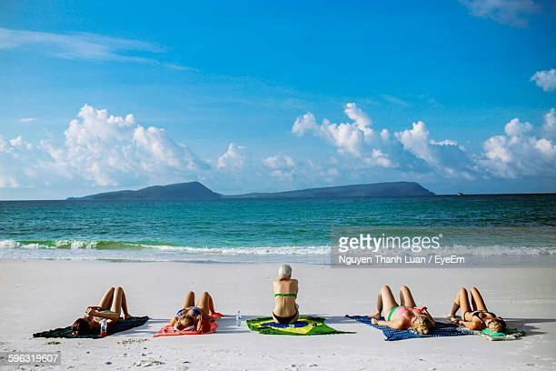 women on beach - women sunbathing stock photos and pictures