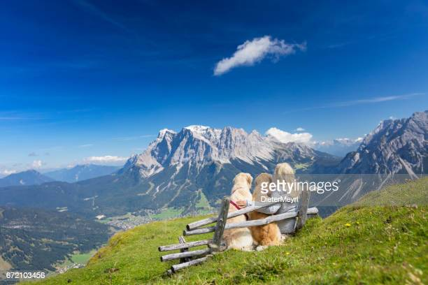 Women on Bench enjoy view with her dogs - Zugspitze, Alps