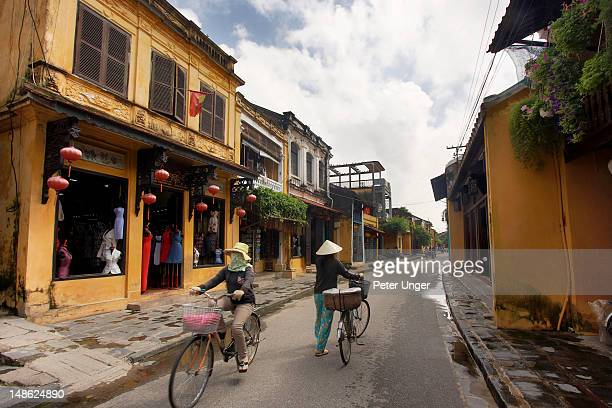 Women on bicycles passing shops on Tran Phu street in Old Town.