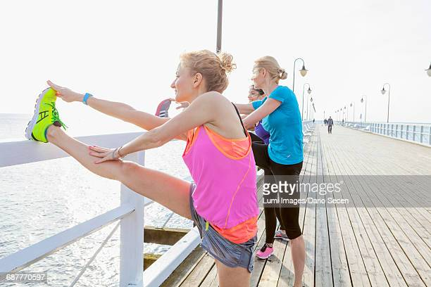 women on jetty stretching legs - pomorskie province stock photos and pictures