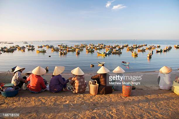 Women on path above beach and fishing boats moored in sea.