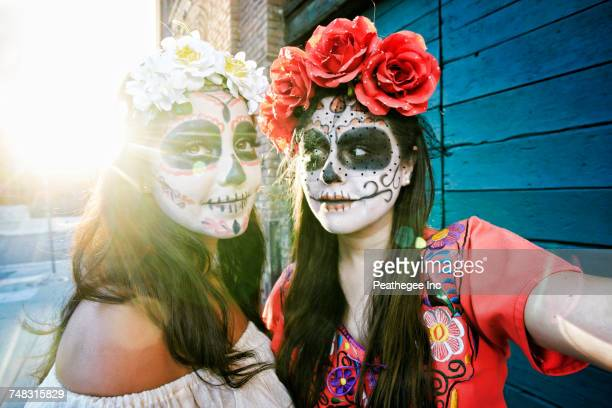 women on sidewalk wearing skull face paint - day of the dead stock pictures, royalty-free photos & images