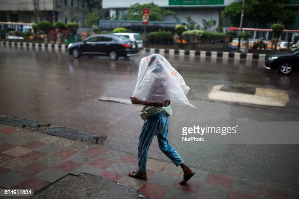 A women on street using poly bag to save from rain drop during rain in Dhaka Bangladesh on July 31 2017