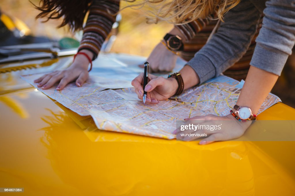 Women on summer road trip reading map for directions : Stock Photo