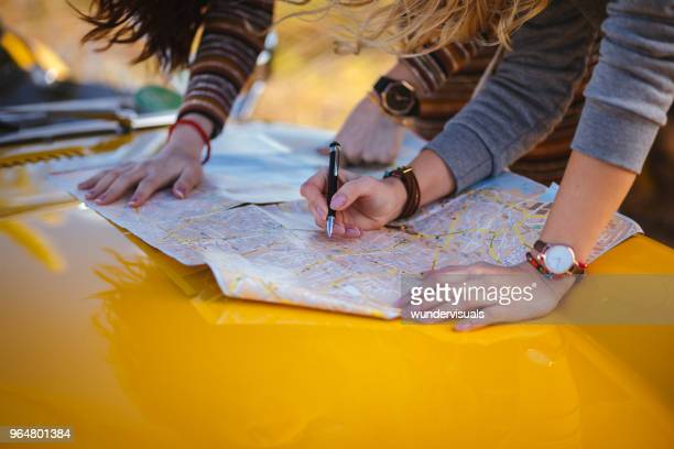 women on summer road trip reading map for directions - cartography stock photos and pictures