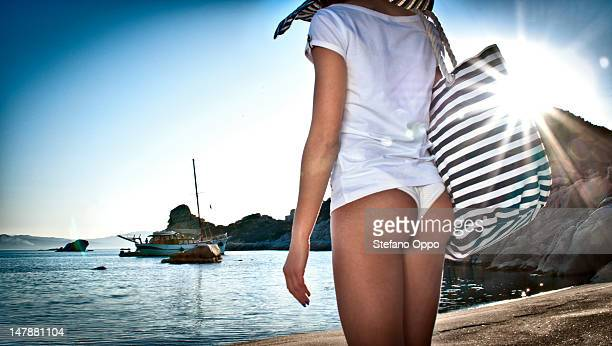 women on the beach looks a sail boat - woman bum stock photos and pictures