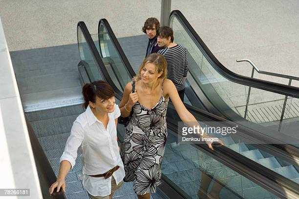 women on the escalator, men looking at them. - down blouse stock photos and pictures