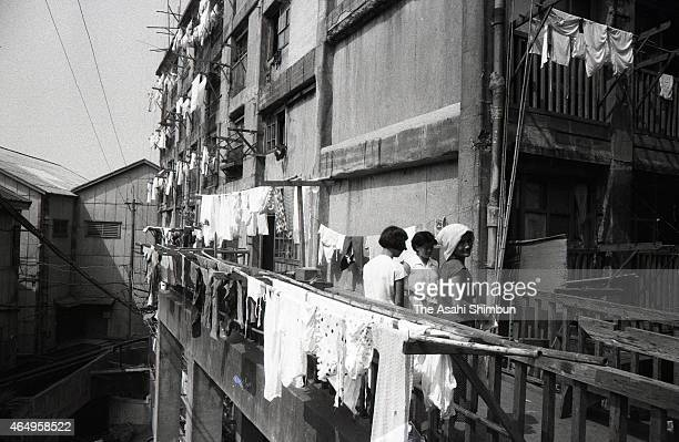 Women on the street spend time under the sun as the concrete apartments are dark at the Hashima on August 12 1956 in Takashima Nagasaki Japan The...