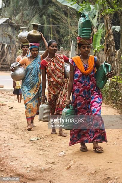 Women on their way home with water filled pitchers collected from a municipal corporation water tank on World Water Day in Gauhati in the...