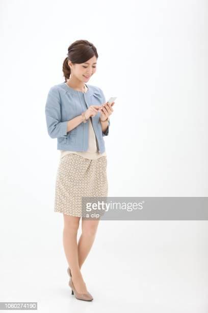 スマートフォンを操作する女性 - 全身 ストックフォトと画像
