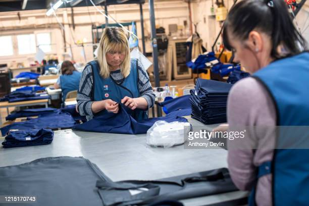 Women pack NHS uniforms as staff at Tibard begin work on a new order of 20,000 nurses uniforms at their factory in Dukinfield where they usually make...