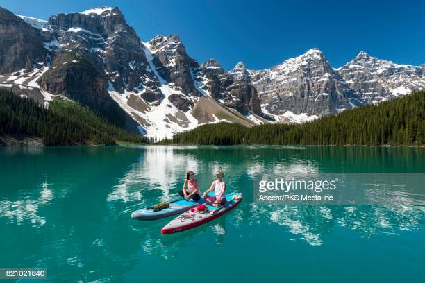 Women paddleboard across mountain lake, sitting