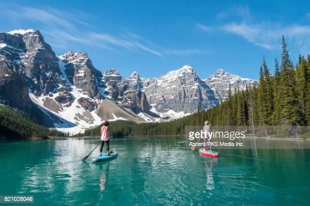 Women paddleboard across mountain lake, standing up
