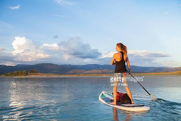Women paddleboarding on scenic lake