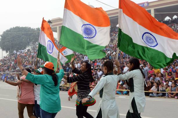 Women parade as they wave Indian national flags during the daily beating of the retreat ceremony at the IndiaPakistan Wagah Border Post some 35kms...