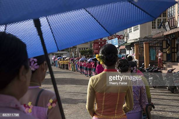 Women parade in traditional clothes during a Buddhist ceremony