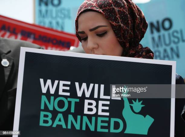 Women participates in demonstration against U.S. President Trump's travel ban as protesters gather outside the U.S. Supreme Court following a court...