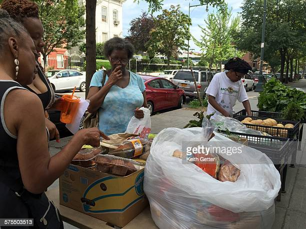 Women participating in a church sponsored community food drive and free give-away of fresh produce and baked goods on a public sidewalk in Fort...