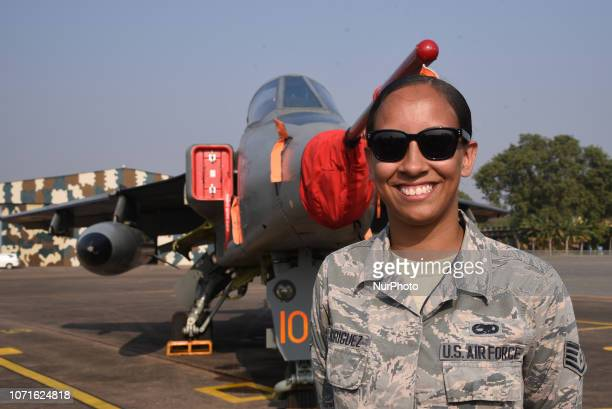 A women Participating member from the Indian Air Force Hawk aircraft stand at the front of of US F15 fighter aircrafts are seen taxing on a runway...