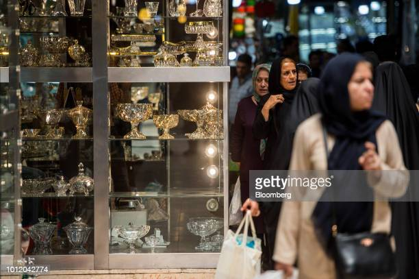 Women pass a store display of glassware while shopping in the Grand Bazaar in Tehran Iran on Monday Aug 6 2018 Irans central bank acting on the eve...