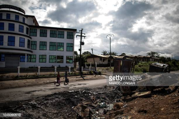Women pass by the edge of the abandoned market into the majority anglophone South West province in Buea on October 3 2018 next the wreckage of a car...