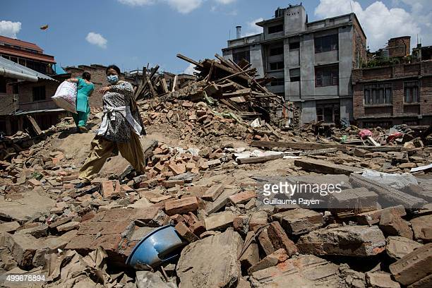 Women pass through the rubbles caused by the collapsed building in the Maru Tole District of Bhaktapur after the violent earthquake who hit Nepal one...