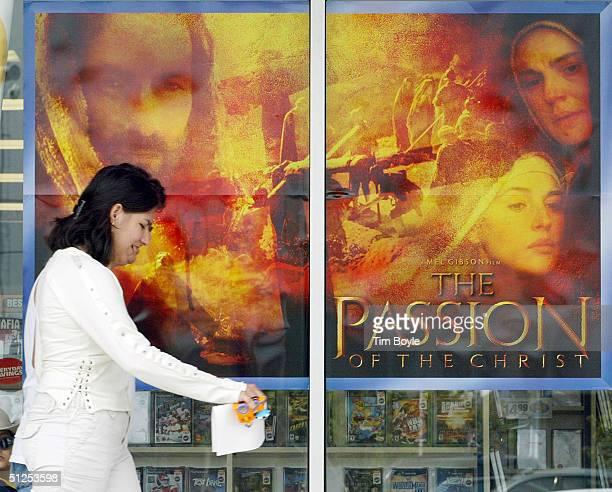 A women passes a video store window with a sign for Mel Gibson's movie 'The Passion of the Christ' at a movie rental store September 1 2004 in Niles...