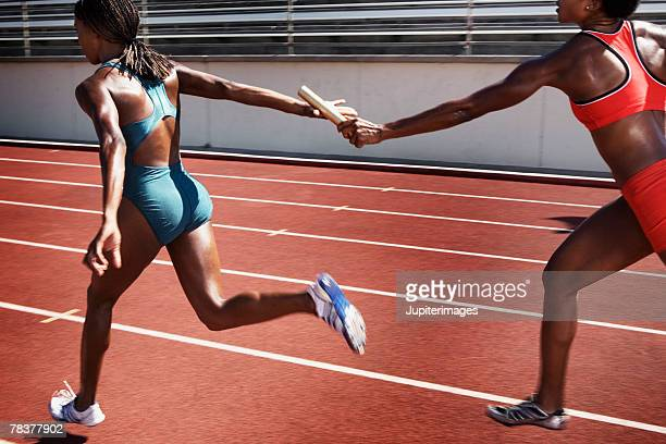 women passing baton to each other during race - passing sport stockfoto's en -beelden
