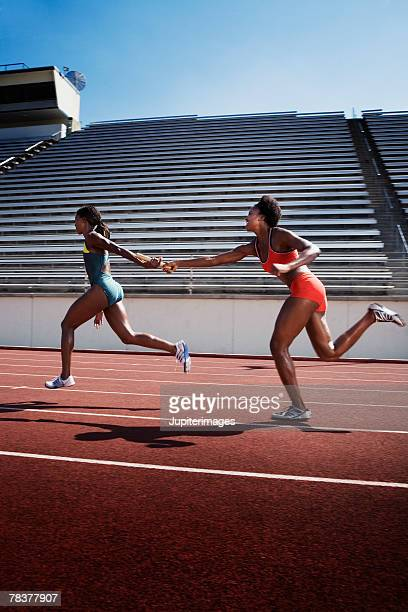 women passing baton to each other during race - passing sport imagens e fotografias de stock