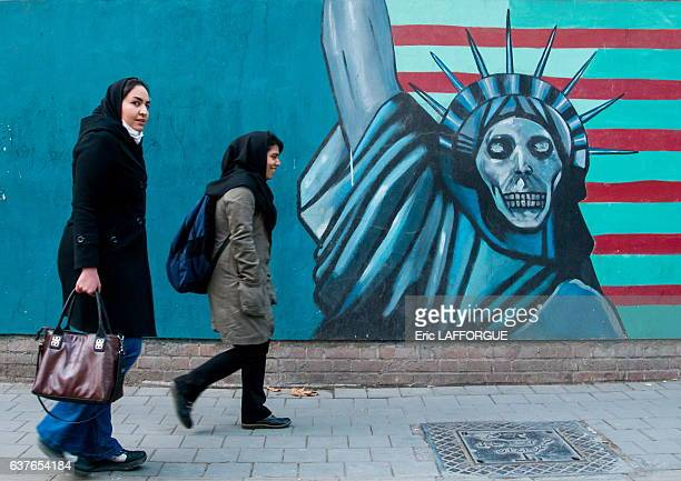 Women passing in front of anti-american mural propoganda on the wall of the former United States embassy in the Central District on December 20, 2015...