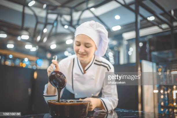 women pastry chef preparing chocolate sauce - chocolate making stock pictures, royalty-free photos & images