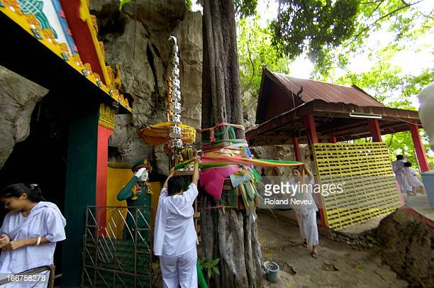 Women pay respect to a sacred tree by wrapping around colorful pieces of cloth at the entrance to the Wat Tham Bo Ya cave. During Khao Phansa ,...