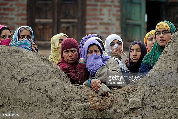 Women peep from the balcony of a house at the encounter site where one militant was killed during a fierce gunfight between militants and Indian army.