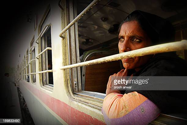 Women peer out of window while the train stops at a railway station in Qasoor which is a small city, only two hours away from the historical city of...