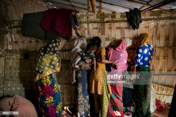 COX'S BAZAR BANGLADESH NOVEMBER 27 Women peer through the wall separating men from women on the day of the wedding of Farmina Begum to 18 year old...