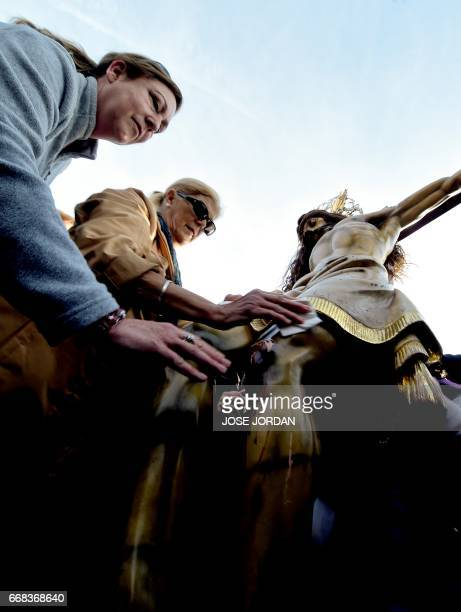 """Women Penitents of """"Cristo Salvador"""" brotherhood touch an effigy of Jesus Christ during a Holy week procession on April 14,2017 at the beach in..."""